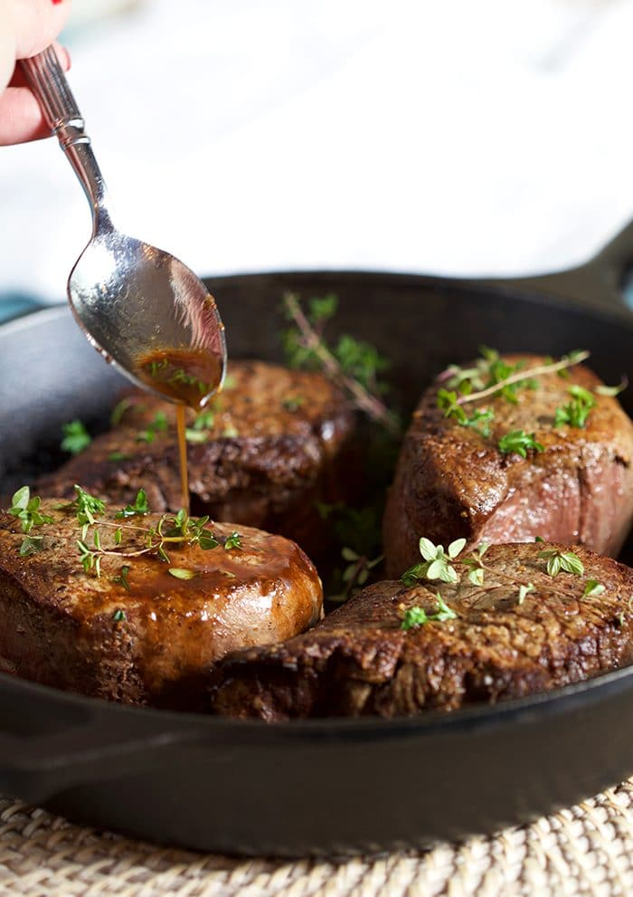 Filet mignon in a cast iron skillet with pan juices being spooned over the steak.