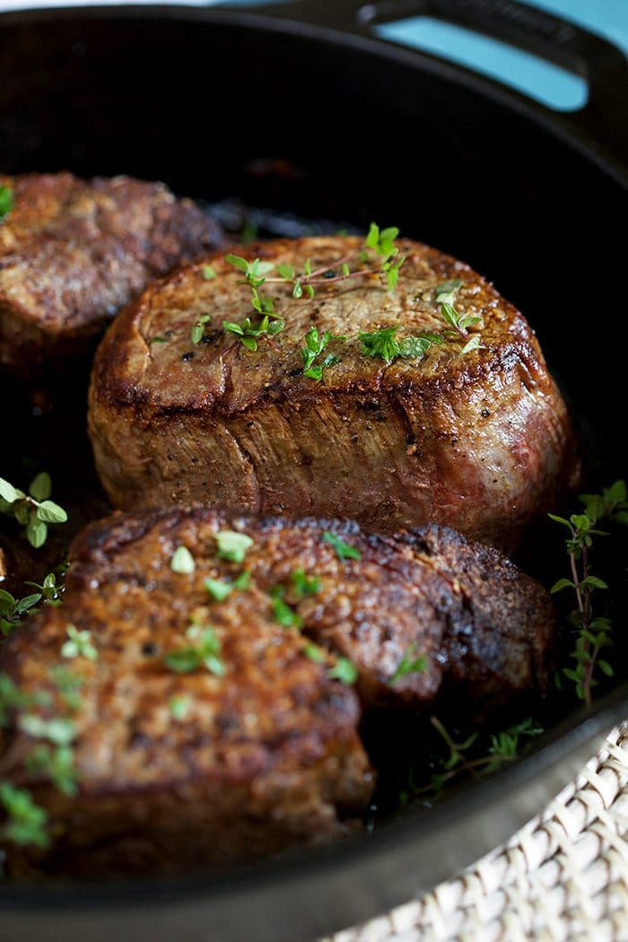 Close up shot of filet mignon in a cast iron skillet.