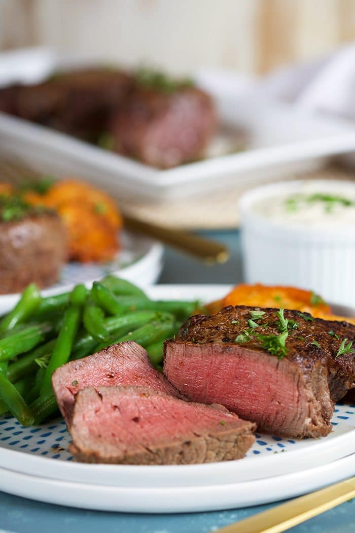 Filet Mignon sliced on a white plate with green beans.