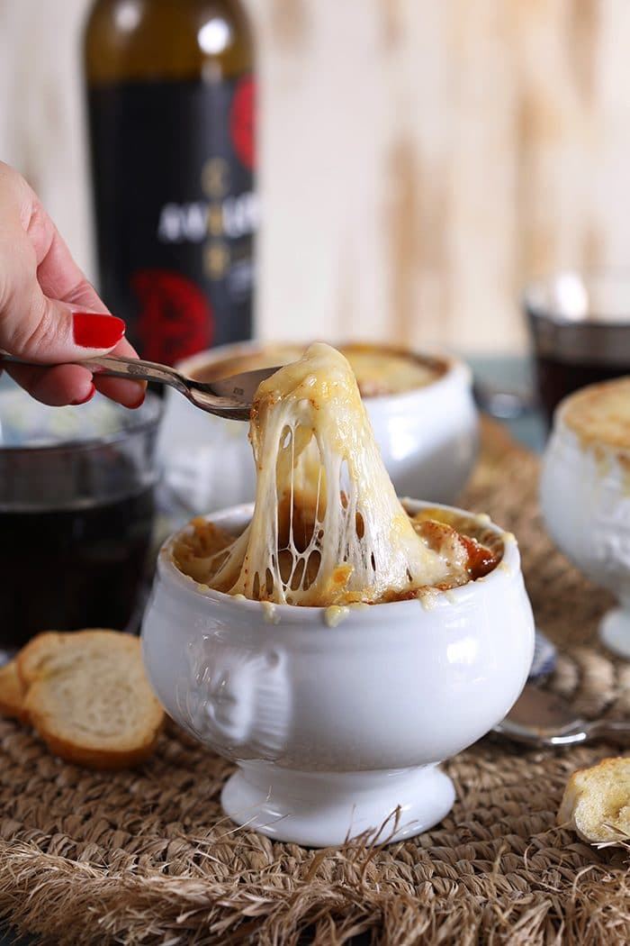French onion soup in a white crock with stretchy cheese pull on a silver spoon. Bottle of red wine in the background on a blue table.
