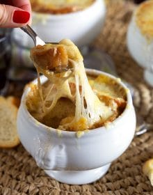 Baked French Onion Soup with a spoon pulling on the melty cheese.