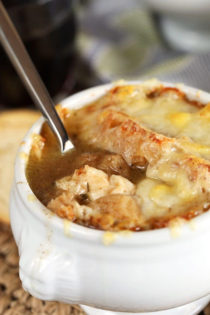 Close up of Baked French Onion Soup with a silver spoon dipped into the soup.