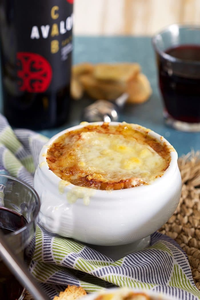 Close up of baked French onion soup in a white crock with a bottle of red wine.