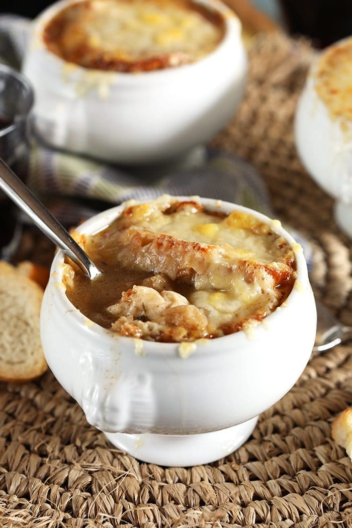 Close up of Classic French Onion Soup in a white crock on a straw placemat.