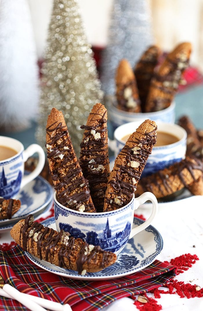 Gingerbread Biscotti with chocolate and crystalized ginger in a blue and white mug on a red plaid napkin.