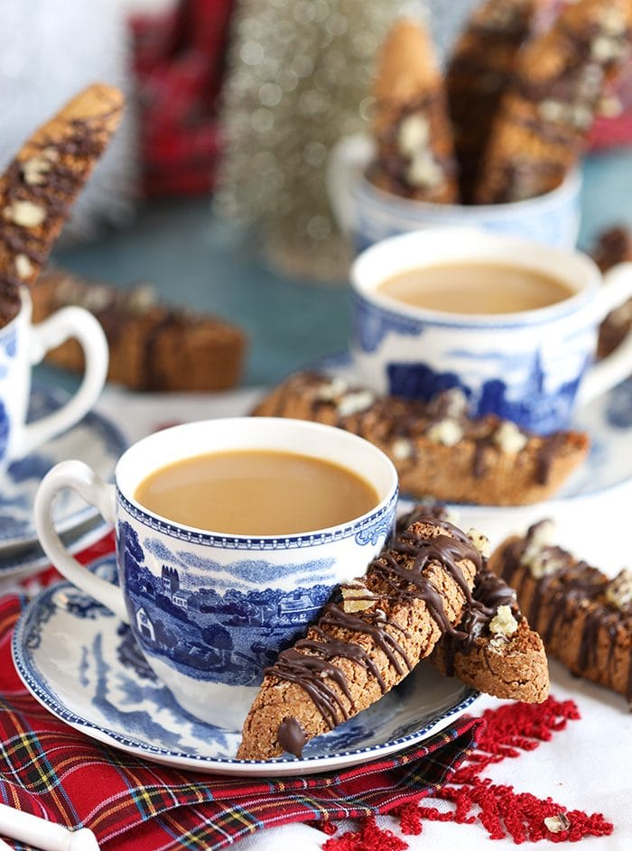 Cup of coffee in a blue and white mug with gingerbread biscotti on the side.