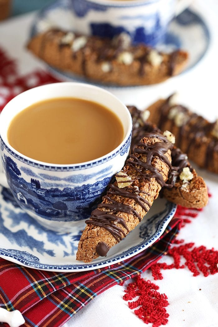 Gingerbread Biscotti on the side of a saucer with a cup of coffee.