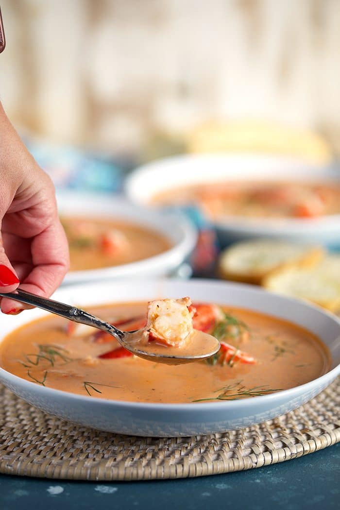 Lobster Bisque in a white shallow bowl with a spoonful of lobster above it.