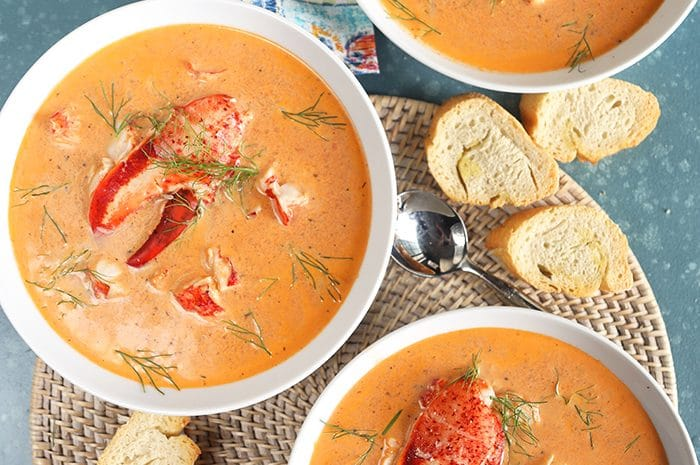 Overhead shot of three white bowls filled with lobster bisque with lobster claws in the center of each bowl and a broken baguette on the side.