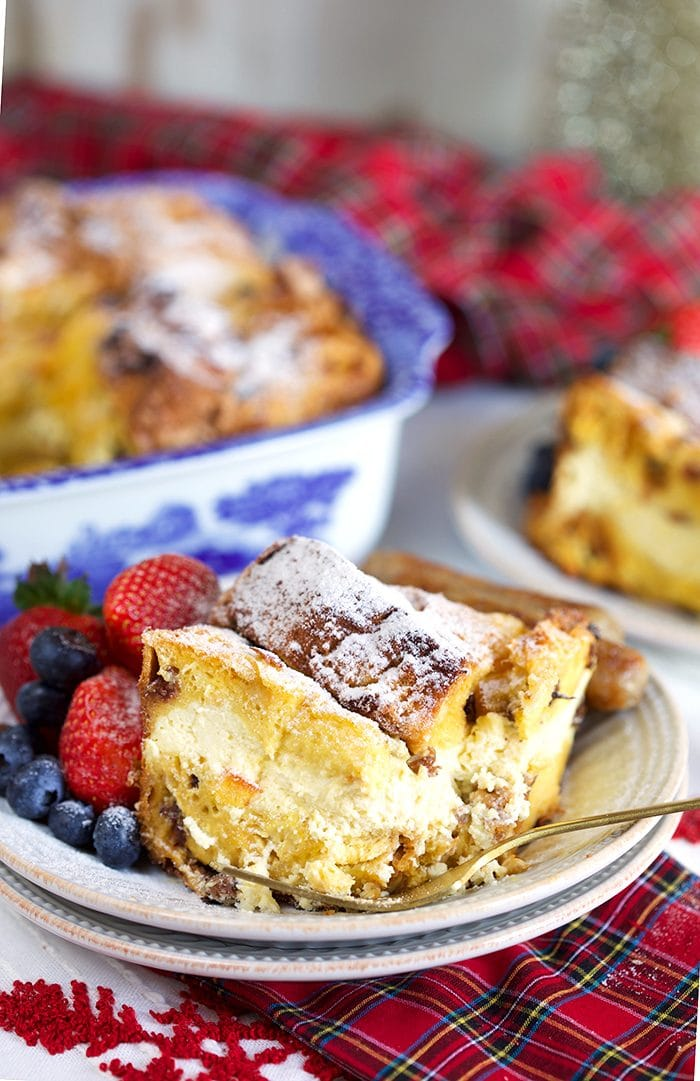 Cheesecake stuffed Panettone French Toast Casserole on a white plate with a gold fork and a plaid napkin. | ThesuburbanSoapbox.com