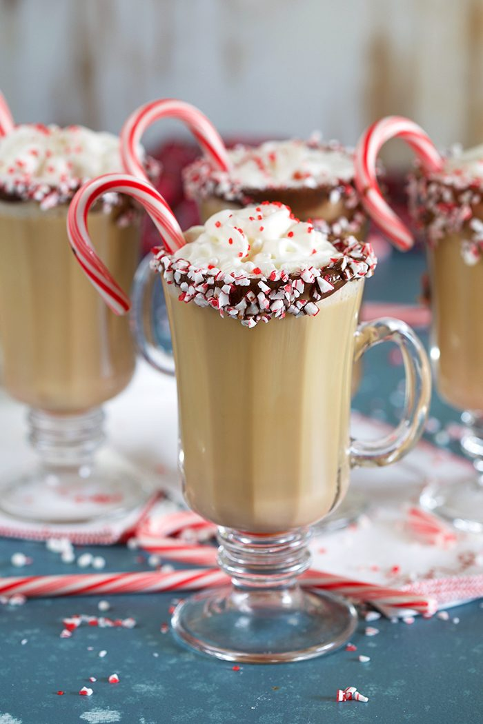 Spiked Peppermint Mocha in a glass mug with whipped cream and a candy cane.