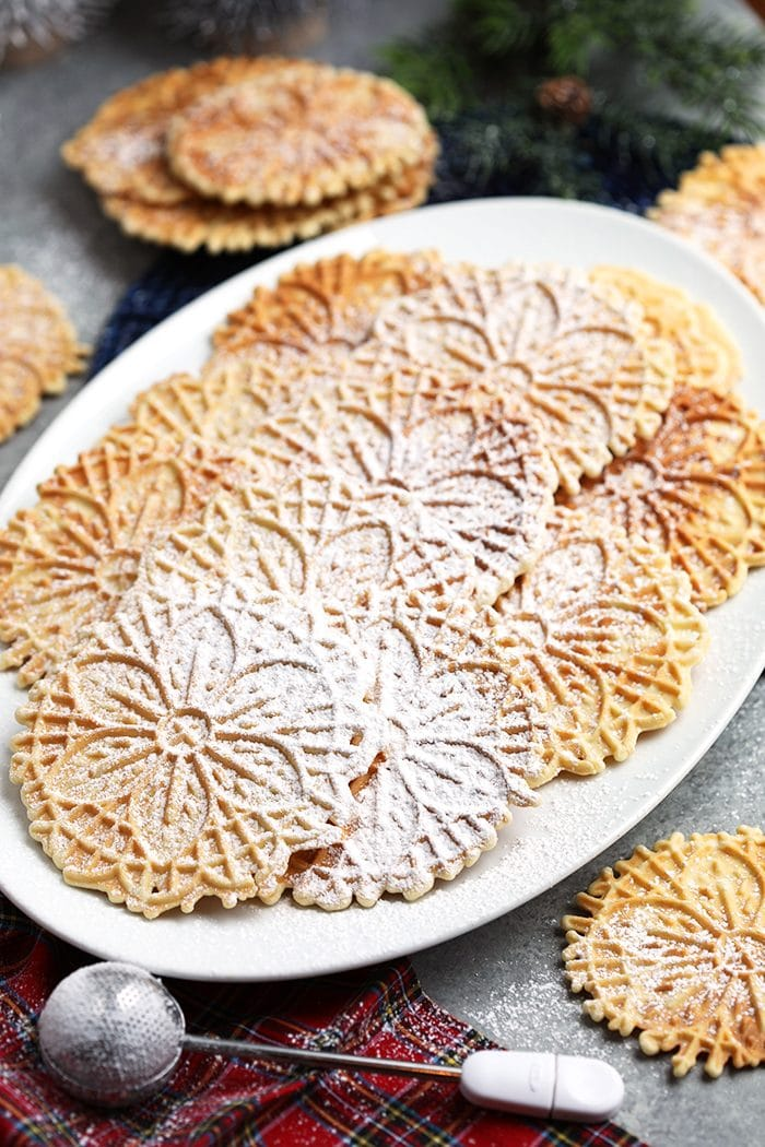 Platter of pizzelles on a white platter with a sugar wand on a plaid napkin.
