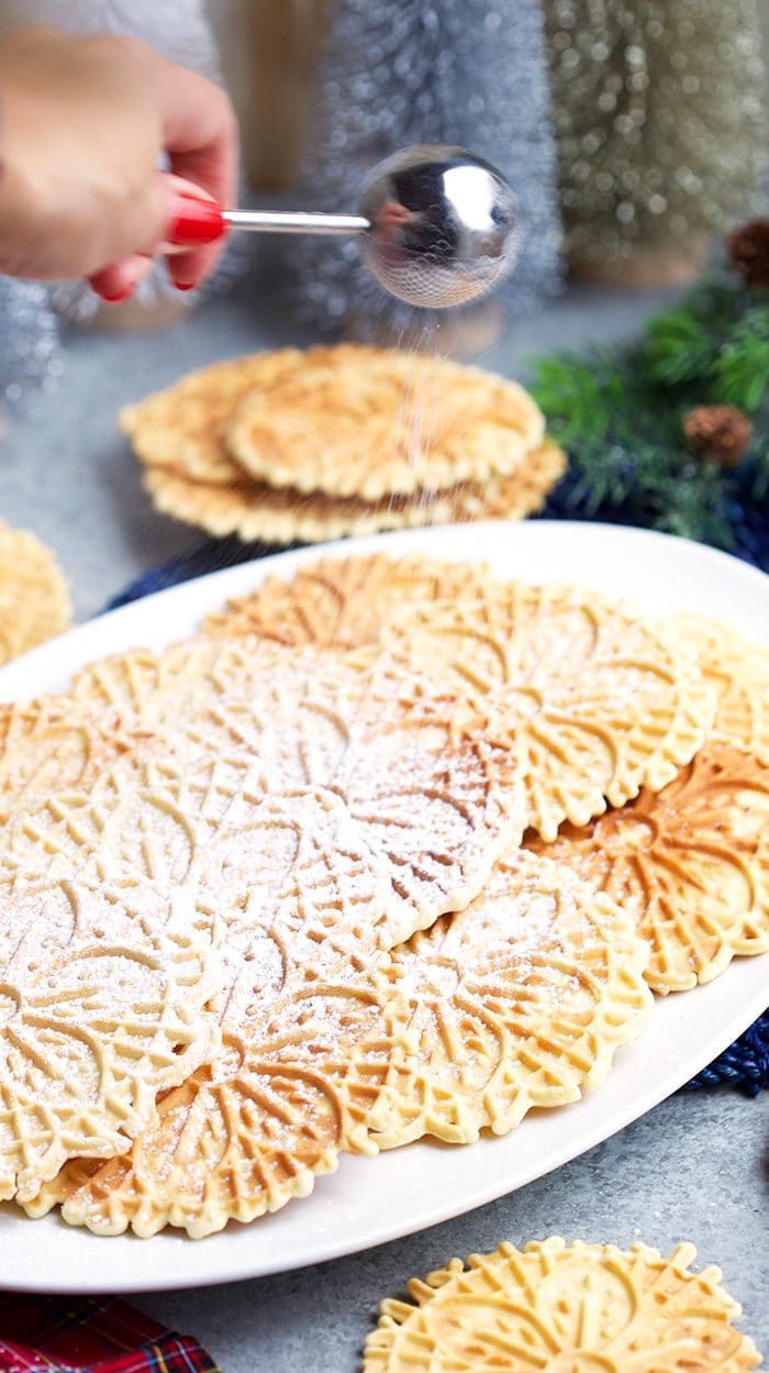 Powdered sugar wand sprinkling sugar over a platter of homemade pizzelles on a white platter.
