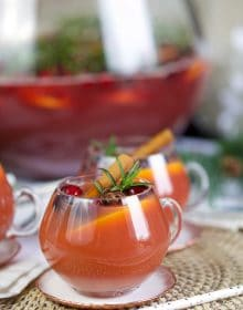 Glass of sparkling pomegranate rum punch with cinnamon sticks, rosemary and cranberry.