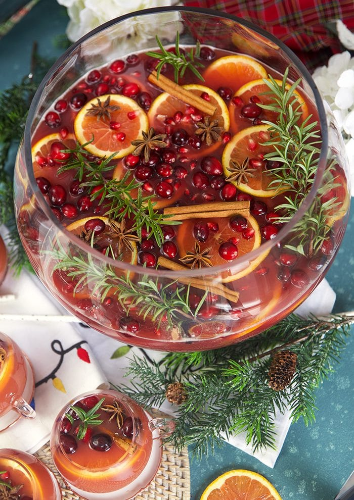 Sparkling Pomegranate Rum Punch in a glass punch bowl with rosemary sprigs and orange slices.