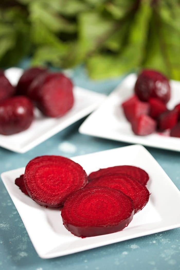 White square plate with sliced roasted beets.