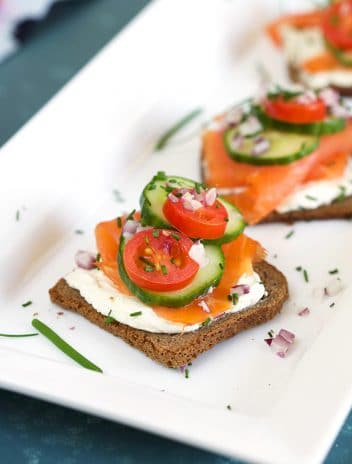 Smoked Salmon on a slice of pumpernickel with cream cheese and chives on a white platter.