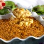 Baked Cauliflower Mac and Cheese in a blue baking dish with a crispy top and a spoonful being held above it.