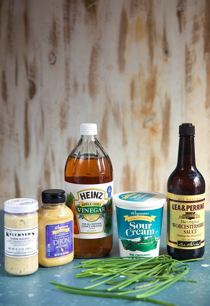 Ingredients for Creamy Horseradish Sauce, a bottle of horseradish, dijon mustard, apple cider vinegar, sour cream Worcestershire sauce and chives.