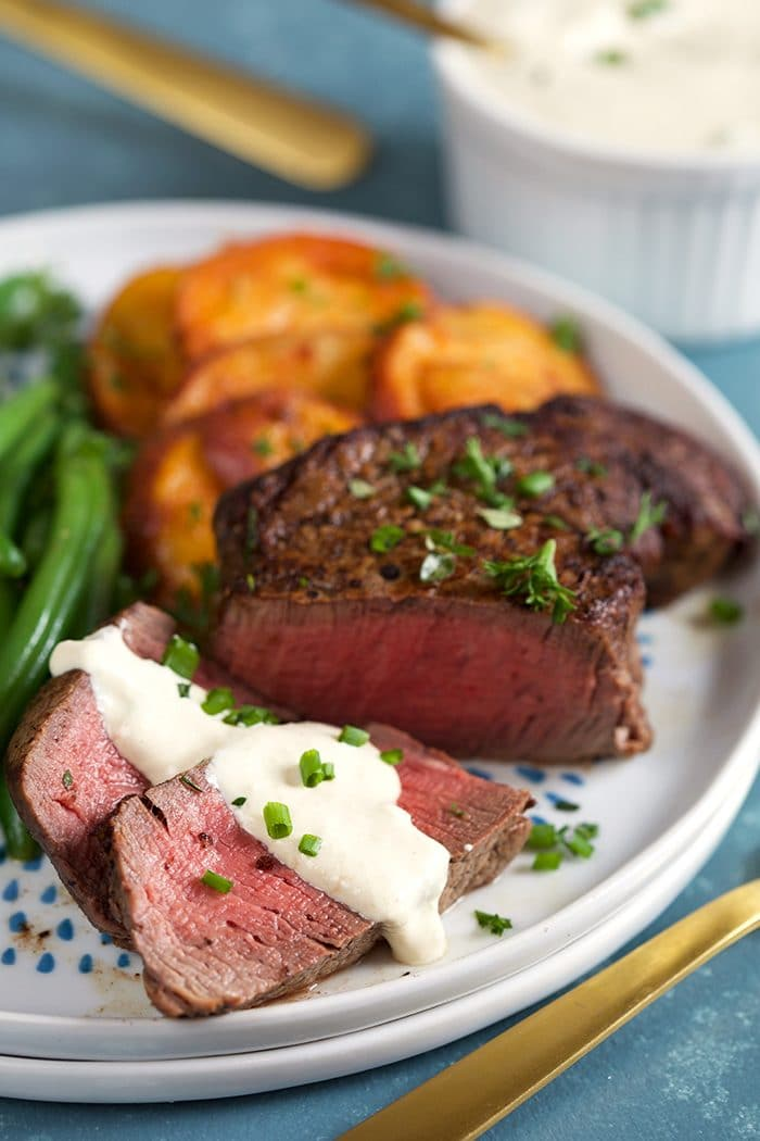 Filet Mignon sliced with creamy horseradish sauce drizzled over top on a white plate with green beans and potatoes.
