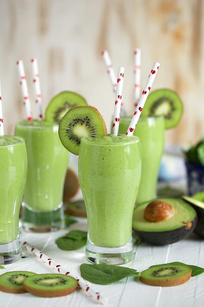 Kiwi Pineapple Spinach Smoothies with avocado half and straws with hearts on them.