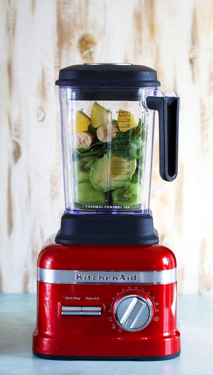 Kiwi Pineapple Spinach Smoothie ingredients in the pitcher of a KitchenAid Red Proline Blender.