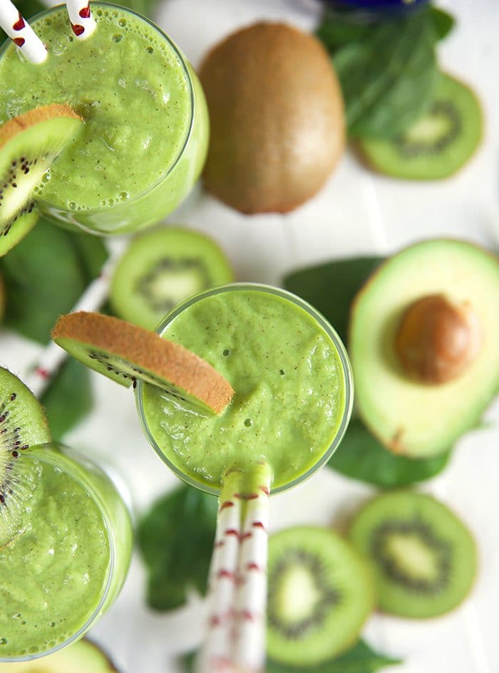 Overhead shot of Kiwi Pineapple Spinach Smoothie with avocado half and kiwi slices.
