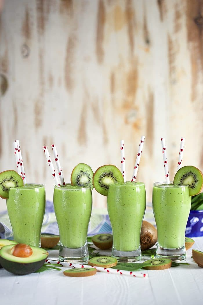 Four kiwi Pineapple Spinach Smoothies in a row with white straws with hearts on them.