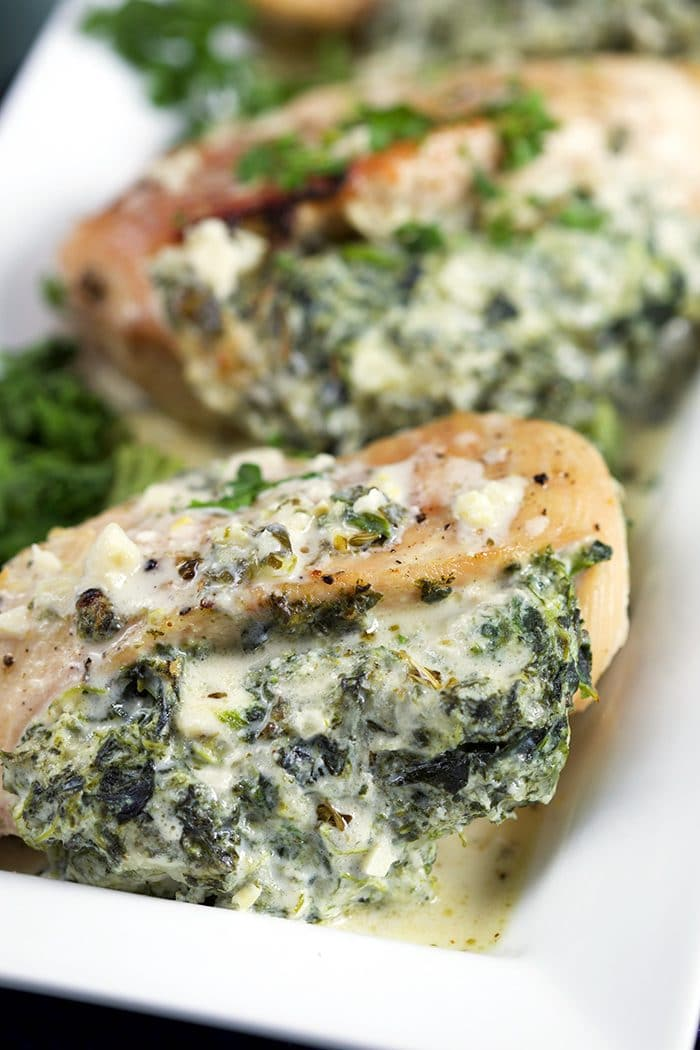 Cheesy Spinach Stuffed Chicken Breast close up on a white platter.