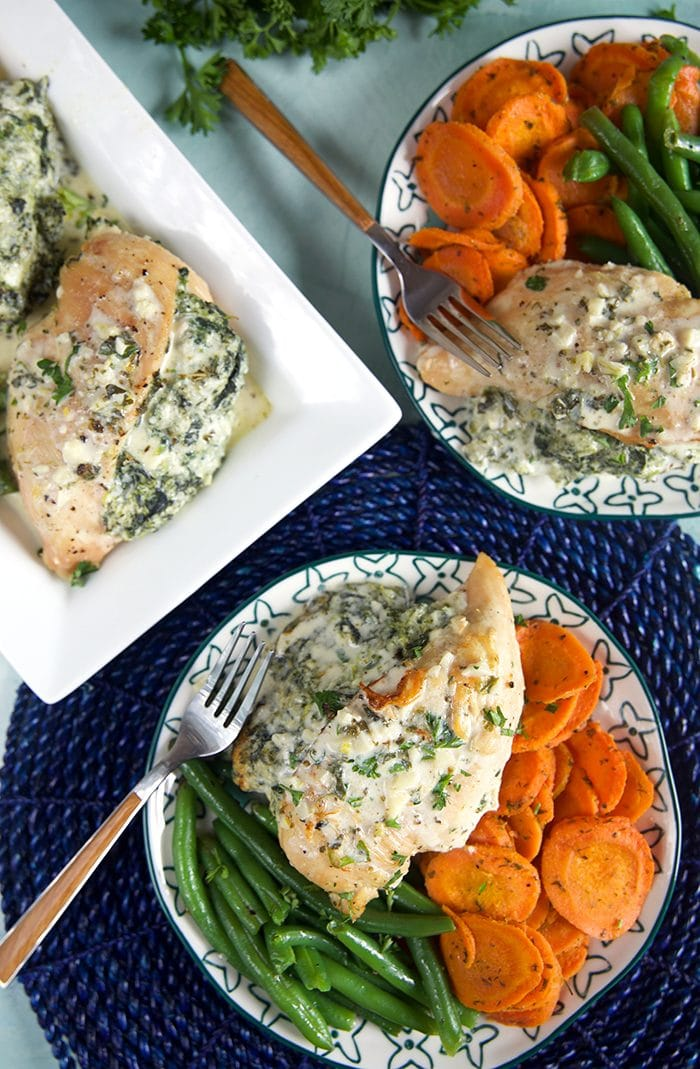 Overhead shot of spinach stuffed chicken breasts on plates with carrots and green beans.