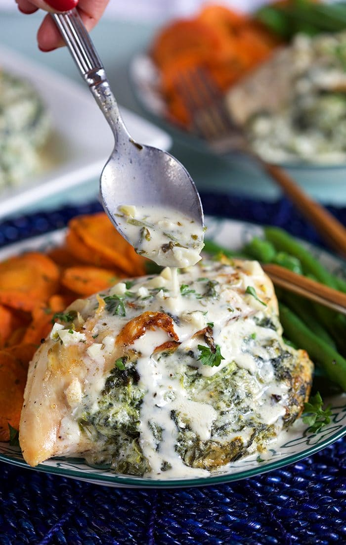 Close up of Spinach Stuffed Chicken being drizzled with parmesan garlic sauce with a silver spoon.