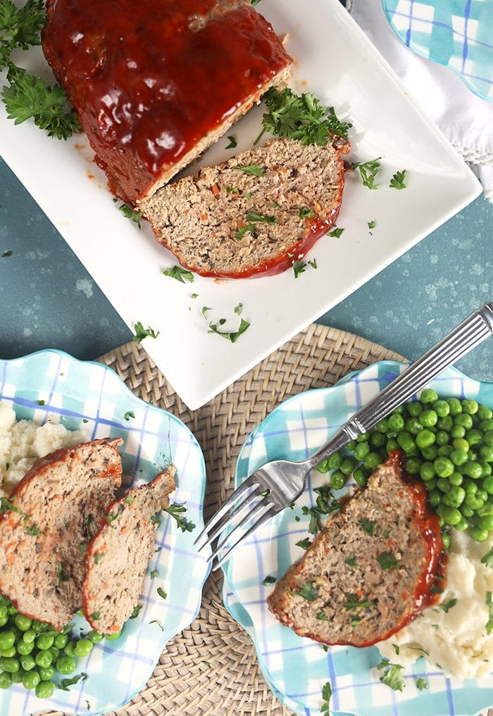 Overhead shot of turkey meatloaf on a white platter with two servings on plaid plates with mashed potatoes and peas.