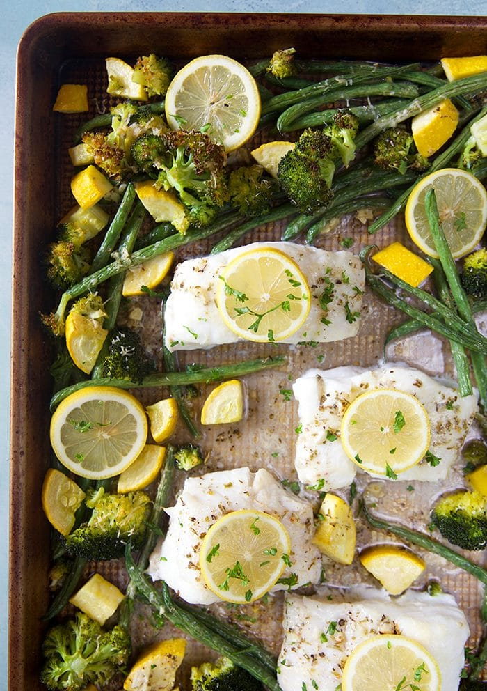 Overhead shot of lemon baked cod on a baking sheet with vegetables after being baked in the oven.
