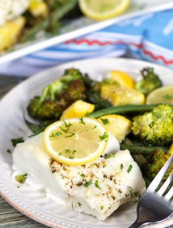 Lemon Baked Cod with a lemon slice on top and a pile of green veggies on a white plate with a fork.