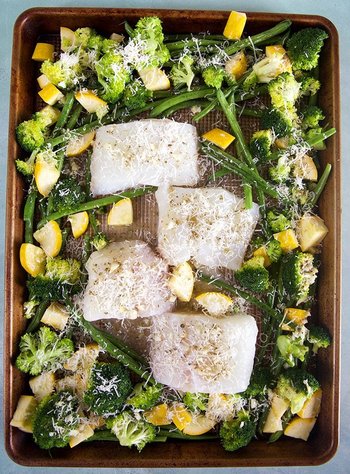 Overhead shot of cod and vegetables on a baking sheet ready to go into the oven.