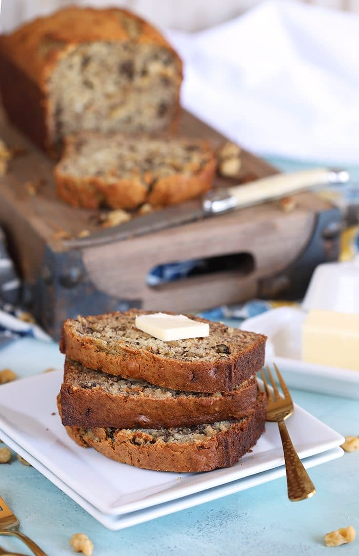 Banana Nut Bread on a brown cutting board with a three stacked slices of bread on a white plate.