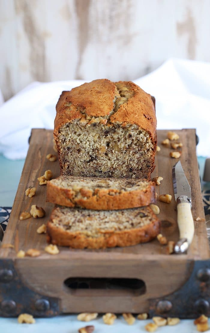 Banana Nut Bread on a cutting board with two slices and a white knife.