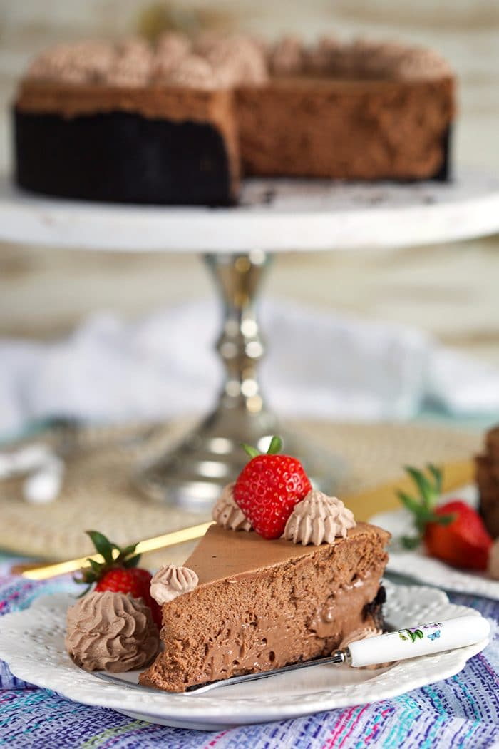 Slice of chocolate cheesecake with a strawberry on top on a white plate with a whole chocolate cheesecake on a marble cake plate in the background.