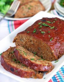 Crockpot meatloaf on a white platter with a striped towel underneath.