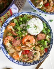 Overhead shot of seafood gumbo with rice in a blue and white bowl.