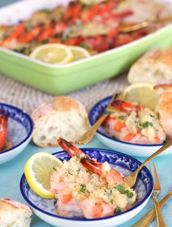 Baked Shrimp Scampi on a blue and white plate with a gold fork.