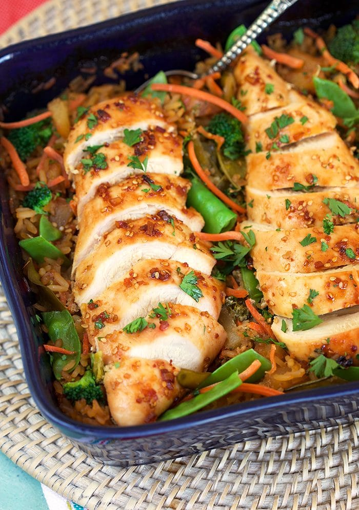 Close up of sliced baked chicken breast in a casserole dish with rice and veggies.