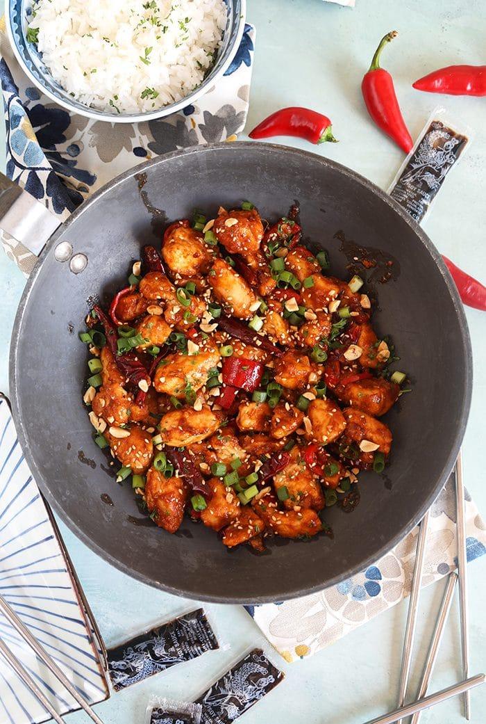 Overhead shot of szechuan chicken in a black wok.