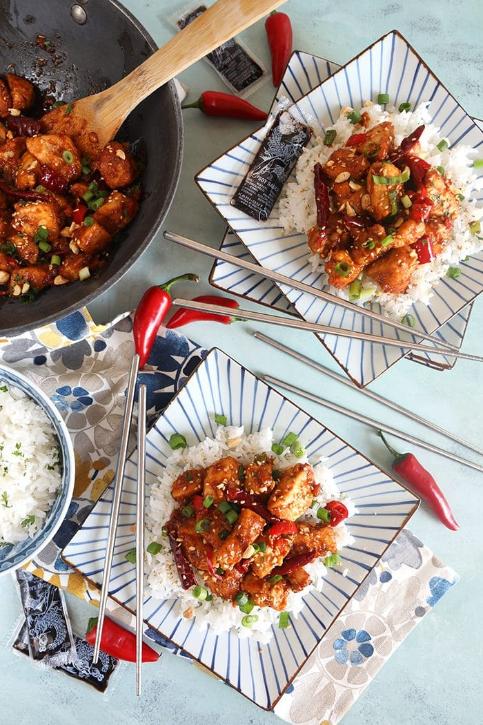 Overhead shot of szechuan chicken on two square plates with white rice and a wok.