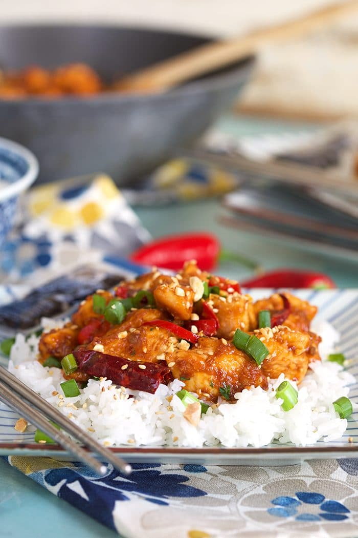 Szechuan chicken on a bed of white rice with silver chopsticks and a packet of soy sauce on the side.