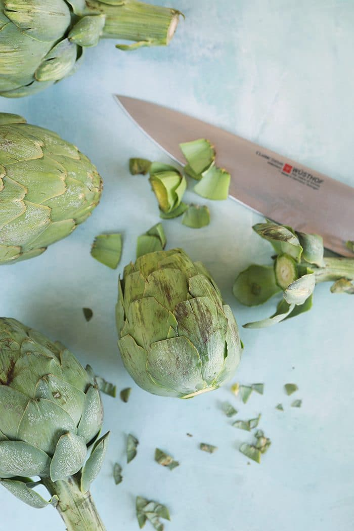 Trimmed artichokes on a blue background with a Wustof knife.
