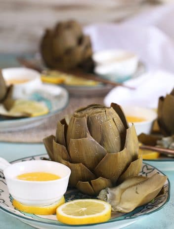 Instant Pot artichokes on a plate with lemon slices and melted butter.