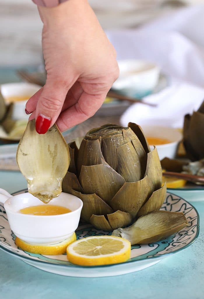 Instant Pot Artichoke on a plate with a hand dipping a leaf into melted butter.