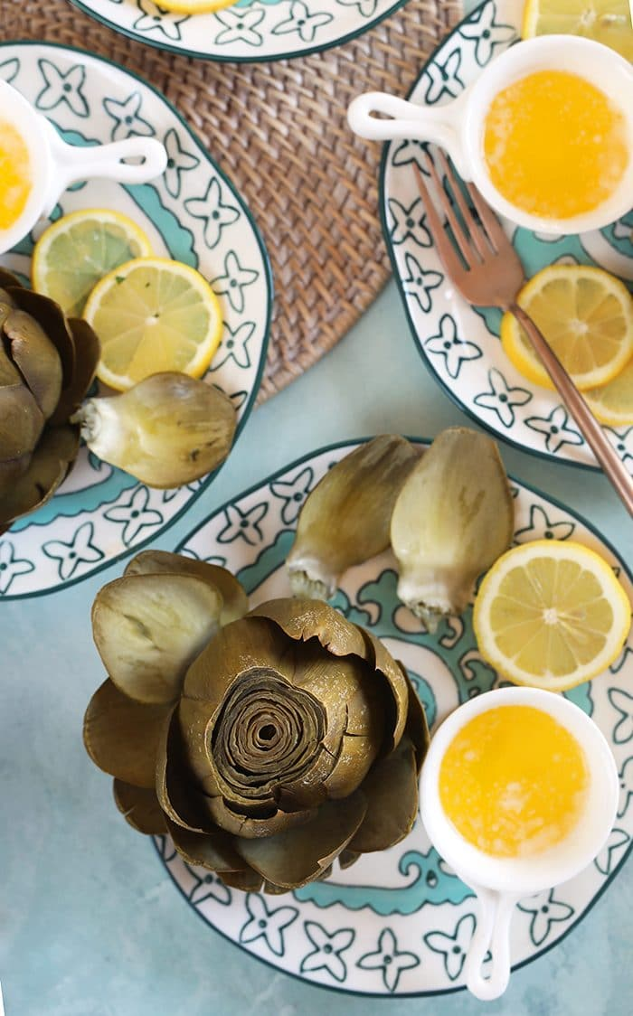Overhead shot or Instant Pot Artichokes with butter in a white dish.