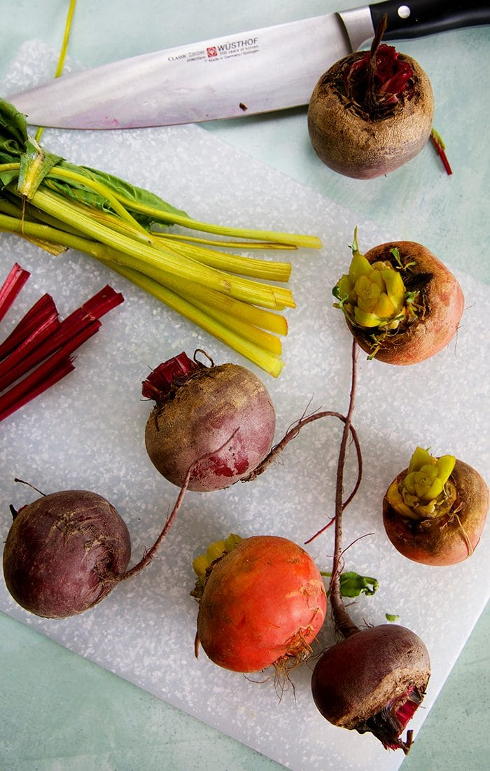 Beets on a cutting board with the tops cut off.